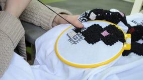 De vrouw borduurt met de hand Oekraïens borduurwerk op witte stof met zwarte woldraden in de hoepel juiste mening stock footage