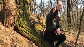 De vrouw in bos wordt verloren zit dichtbij boom en onderzoekssignaal op mobiele telefoon die stock videobeelden