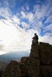 De vrouw bovenop de berg bereikt voor de zon Royalty-vrije Stock Afbeeldingen