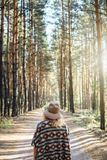 De vrouw breed-brimmed binnen vilten hoed en authentieke poncho die zich op een landweg in de bos Verticale richtlijn van de mist stock foto