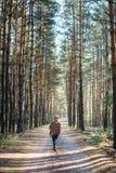De vrouw breed-brimmed binnen vilten hoed en authentieke poncho die zich op een landweg in de bos Verticale richtlijn van de mist royalty-vrije stock foto