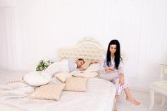 De vrouw controleert gemeen haar echtgenoot` s telefoon, terwijl hij slaapt royalty-vrije stock afbeelding