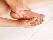 De vrouw controleert haar pijnlijke voet stock afbeelding