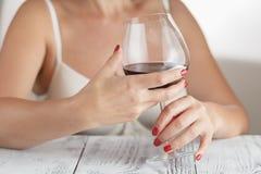 De vrouw controleert rode wijn Stock Fotografie