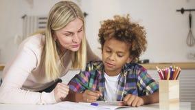 De vrouw controleert van tijd tot tijd het huiswerk van vrolijke, aantrekkelijke zoon stock video