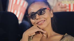De vrouw in 3D glazen houdt haar hand dichtbij haar kin bij de bioscoop stock footage