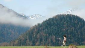 De vrouw in de rustieke kleding spint rond op de weide bij de achtergrond van de groene bergen stock videobeelden