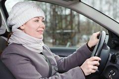 De vrouw in de winter kleedt drijfauto stock fotografie
