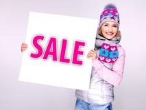 De vrouw in de winterbovenkleding houdt de witte banner met verkoopwoord Stock Afbeelding