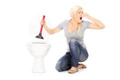 De vrouw deblokkeert een stinky toilet met duiker Stock Foto