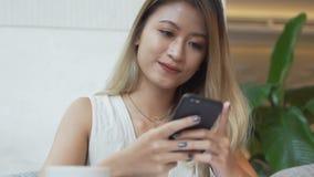 De vrouw denkt wat om in een antwoord aan vriend op smartphone app te schrijven stock video