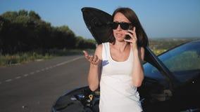 De vrouw dichtbij een gebroken auto op de weg verzoekt hulp Het jonge ongerust gemaakte meisje gebruikt een telefoon om te verkla stock footage