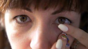 De vrouw die de camera onderzoeken en draagt contactlenzenclose-up stock foto