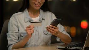 De vrouw die creditcardgegevens ingaan in cel telefoneert, gemakkelijke app voor transacties stock video
