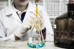 De vrouw die de wetenschapper is doet het experiment, de titratie van de reagens in de fles Stock Afbeeldingen