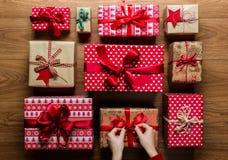 De vrouw die een boog op beautifuly verpakte uitstekende Kerstmis bevestigen stelt op houten achtergrond voor Stock Foto