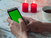 De vrouw die een groene het scherm Slimme Telefoon in koffie met behulp van, sluit omhoog royalty-vrije stock afbeelding