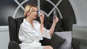 De vrouw die een hand houden houdt een spiegel en het doen van epilation bovenop haar lippen stock footage