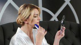 De vrouw die een hand houden houdt een spiegel en het doen van epilation bovenop haar lippen stock videobeelden