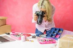 De vrouw die foto's van haar eigen gecreeerde koopwaar nemen, verkoopt hen online en post pakketten aan kopers royalty-vrije stock foto