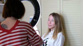 De vrouw die foto van een mooi meisje met mobiele telefoon nemen throung een ring leidde lamp stock video