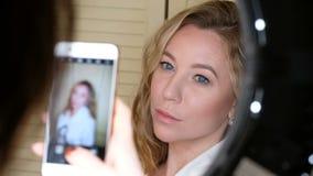 De vrouw die foto van een mooi meisje met smartphone nemen throung een ring leidde lamp stock videobeelden