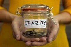 De vrouw die geld voor liefdadigheid verzamelen en houdt kruik met muntstukken royalty-vrije stock afbeeldingen