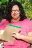 De vrouw die glazen draagt schrijft nota's en glimlacht Stock Foto