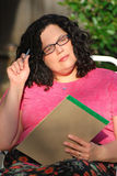 De vrouw die glazen draagt zit en denkt strategie Stock Afbeeldingen