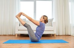 De vrouw die greep van de yoga de dubbele teen doen stelt thuis royalty-vrije stock afbeeldingen