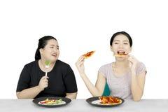 De vrouw die haar vriend bekijken eet pizza stock afbeeldingen