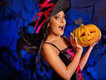 De vrouw die heksenhoed dragen houdt grote oranje pompoen Stock Foto's