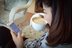 De vrouw die hete koffie in koffie drinken en gebruikt een mobiele telefoon Stock Foto's