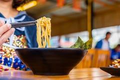 De vrouw die kruidig eten ramen Japanse noedelsoep in een zwarte kleur ramen kom stock afbeeldingen