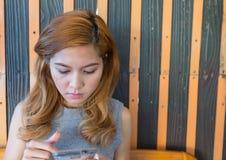 De vrouw die mobiele hand spelen zit Stock Afbeelding