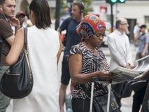 De vrouw die in nationaal kostuum een krant lezen dichtbij de Straatmetro van Liverpool royalty-vrije stock fotografie