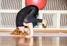 De vrouw die oefeningsyoga doen en pilates stelt op mat in gymnastiek Asana Het concept sport, fitness, opleiding en gezondheid Stock Afbeelding
