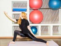 De vrouw die oefeningsyoga doen en pilates stelt op mat in gymnastiek Asana Het concept sport, fitness, opleiding en gezondheid Royalty-vrije Stock Fotografie