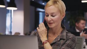 De vrouw die personal computer met behulp van en cellulair aan het spreken met clien stock videobeelden