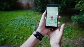 De vrouw die Pokemon spelen GAAT toepassing de klap vergrote werkelijkheids slimme telefoon app terwijl het proberen om Pokemon S stock footage