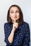 De vrouw die stilte zeggen die stil is met vinger op lippengebaar op grijze muurachtergrond wordt geïsoleerd Portret die van emot royalty-vrije stock foto
