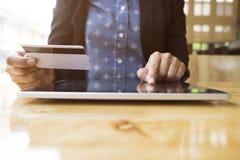 De vrouw die tablet gebruiken aan online het winkelen en betaalt door creditcard Stock Afbeelding