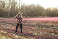 De vrouw die telefoonbeeld nemen die zich op een gebied van de vroege lente bevinden bloeit tegen een vage achtergrond royalty-vrije stock afbeelding