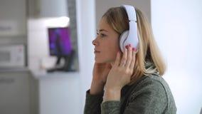 De vrouw die thuis het luisteren goede muziek ontspannen, kleedt hoofdtelefoons stock video