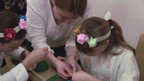 De vrouw die twee tienermeisjes in bloem onderwijzen omrandt hoe te beadwork bij lijst te maken handmade verwezenlijking stock videobeelden