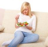 De vrouw die van de blonde gezond voedsel, Griekse salade eet royalty-vrije stock foto
