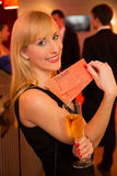 De vrouw die van de blonde kaartjes voor een theater of een overleg voorstellen Stock Fotografie