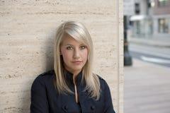 De Vrouw die van de blonde tegen Muur leunt Stock Afbeelding
