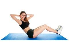 De vrouw die van de geschiktheid aerobics op gymnastiekmat doet Stock Afbeeldingen