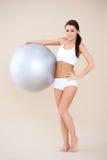 De vrouw die van de geschiktheid zich met gymnastiekbal bevinden Stock Fotografie